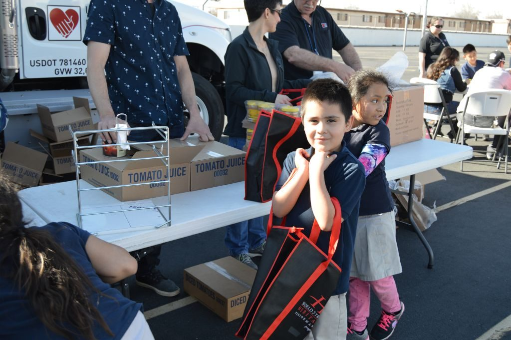Students receive food from a mobile food pantry at their elementary school. The Utah Food Bank organizes these mobile food pantries to get healthy food to more children. (Utah Food Bank)