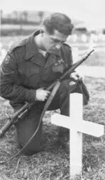 A Canadian soldier kneels at grave