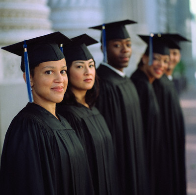 Group of young graduates standing together outdoors smiling