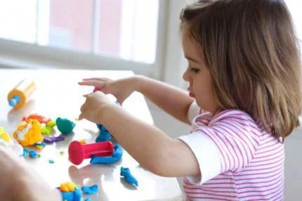 Bambina che gioca con la pasta modellabile