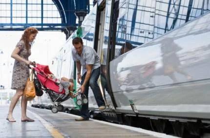 Famiglia con passeggino che sale sul treno
