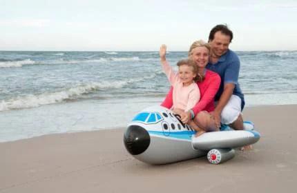 mamma papà e figlia su un aereo gonfiabile  sulla spiaggia