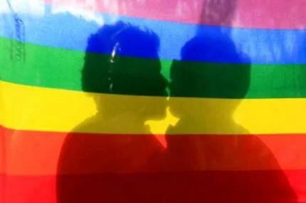 L'ombra di due ragazzi che si baciano si vede attraverso una bandiera arcobaleno