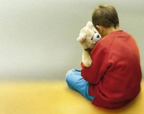 bambino di schiena che abbracci orsetto di peluche