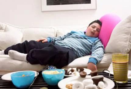 ragazzo grasso sul divano con davanti schifezze da mangiare