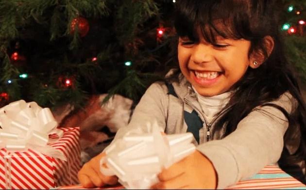 bambina sorride scartando un regalo