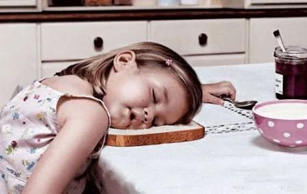bambina addormentata sul tavolo della cucina