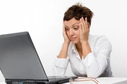 donna di fronte al pc con mani si tocca il vispo in segno di stanchezza