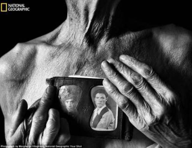 torace di uomo nudo anziano che tiene in mano foto di uomo e donna