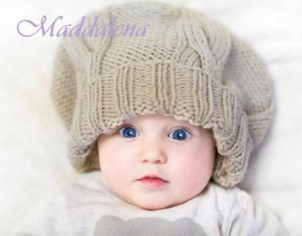 Funny baby in huge knitted hat wearing warm sweater