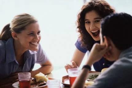 Amici ridono e scherzano attorno ad un tavolo