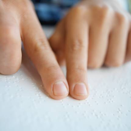 close up view of the fingers of a person reading by Braille
