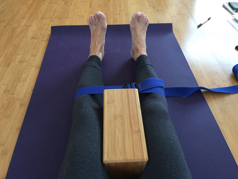 """Place a yoga block between your knees and a yoga strap around your gastrocnemius."""
