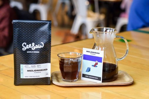 Seesaw's Melonhead coffee packaging with a coffee description card and coffee on a tray