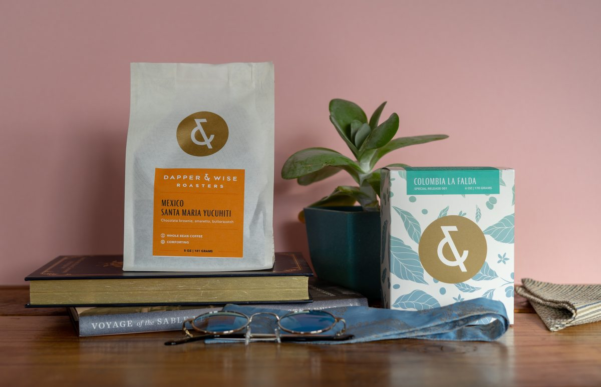 Dapper & Wise coffee bag and box packaging with a plant and books surrounding it