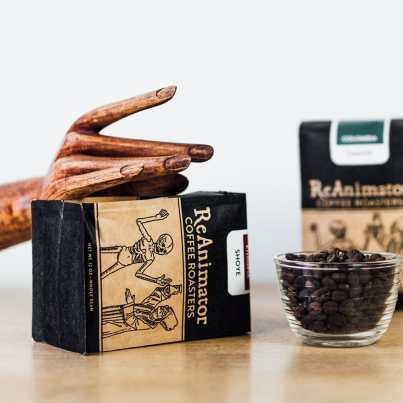 ReAnimator Coffee Roasters with packaging, wooden hand and cup of roasted beans