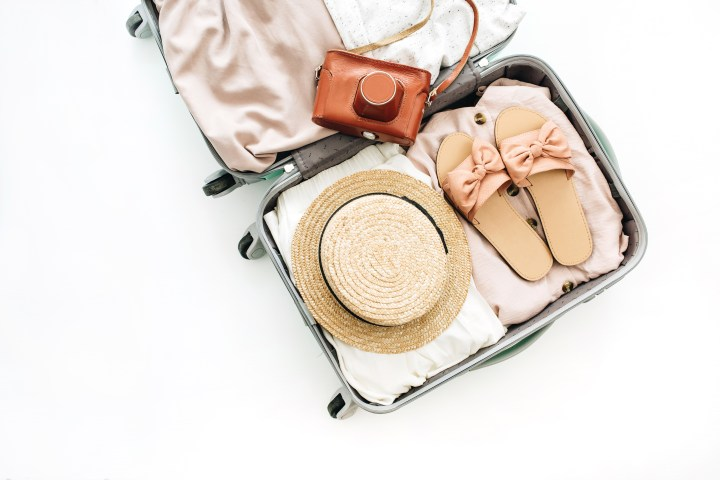 Hand luggage with stylish female clothes and retro camera on white background. Flat lay, top view. Summer fashion clothes and travel concept.