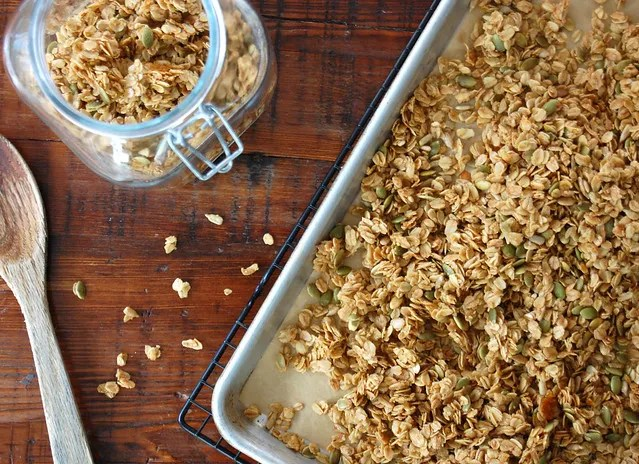 granola on sheet pan with wooden spoon wooden counter