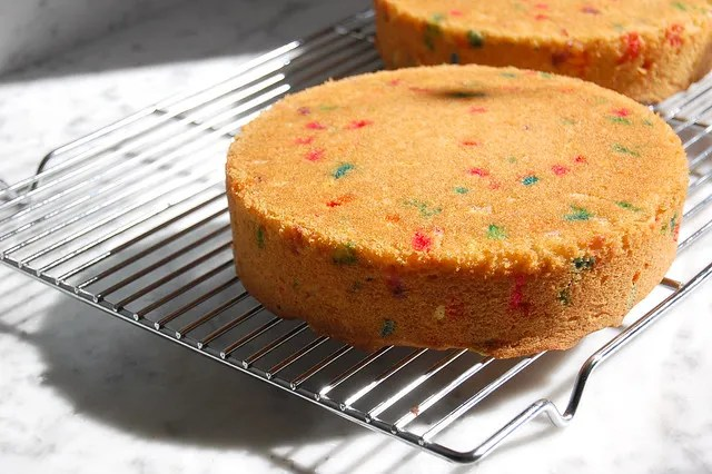 vanilla sprinkle cake on cooling rack with marble counter