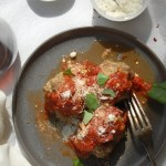 three meatballs with tomato sauce on black plate