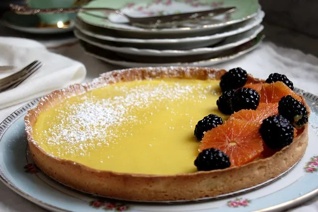 lemon tart with fruit and china dishes