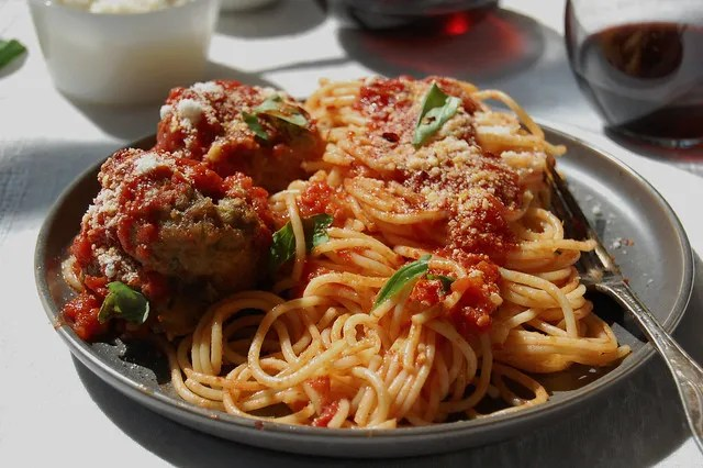 spaghetti and Italian meatballs on dish with red wine