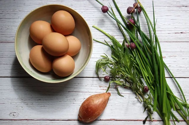 eggs and chives and shallot on white wood board