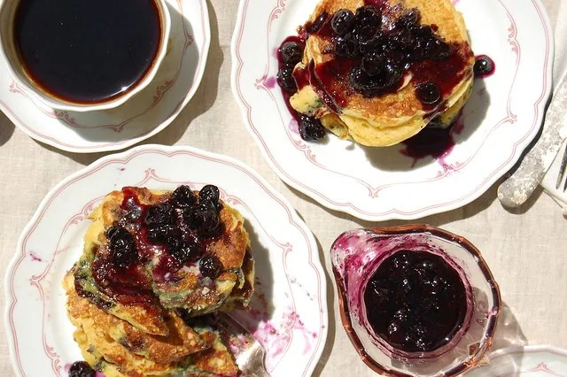 stack of pancakes with blueberry maple syrup and coffee