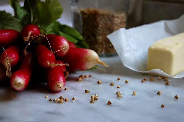 french radishes with butter and buckwheat groats on marble