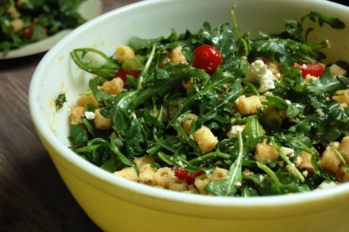 pasta salad in yellow bowl with arugula and pasta and tomato