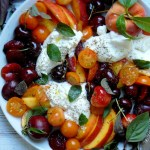 white platter of burrata and stone fruit caprese with basil peaches cherries