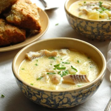 bowls of fish chowder with buttermilk biscuits on white tablecloth
