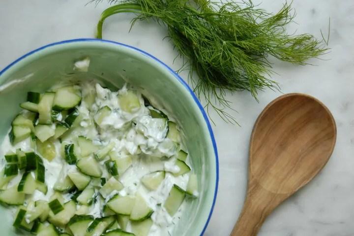 tzatziki ingredients yogurt herbs cucumber on marble