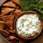 bowl of creamy cucumber tzatziki with pita chips and fresh mint and dill on wood