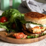 salmon burger with tzatziki on wooden plate with salad