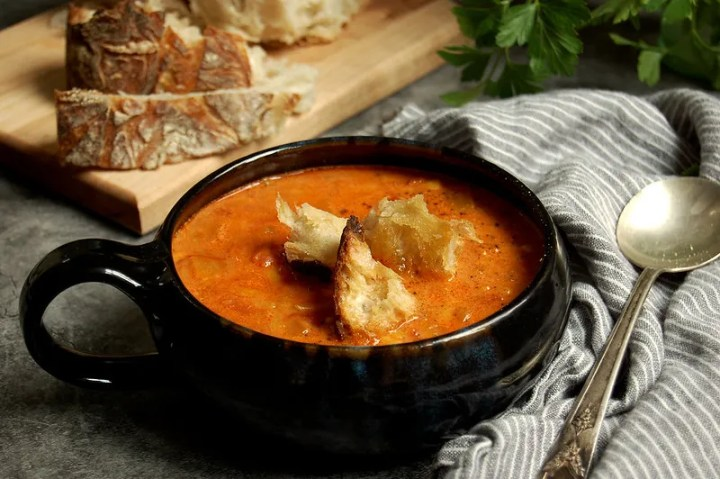 bowl of tomato orzo soup with croutons and bread with spoon