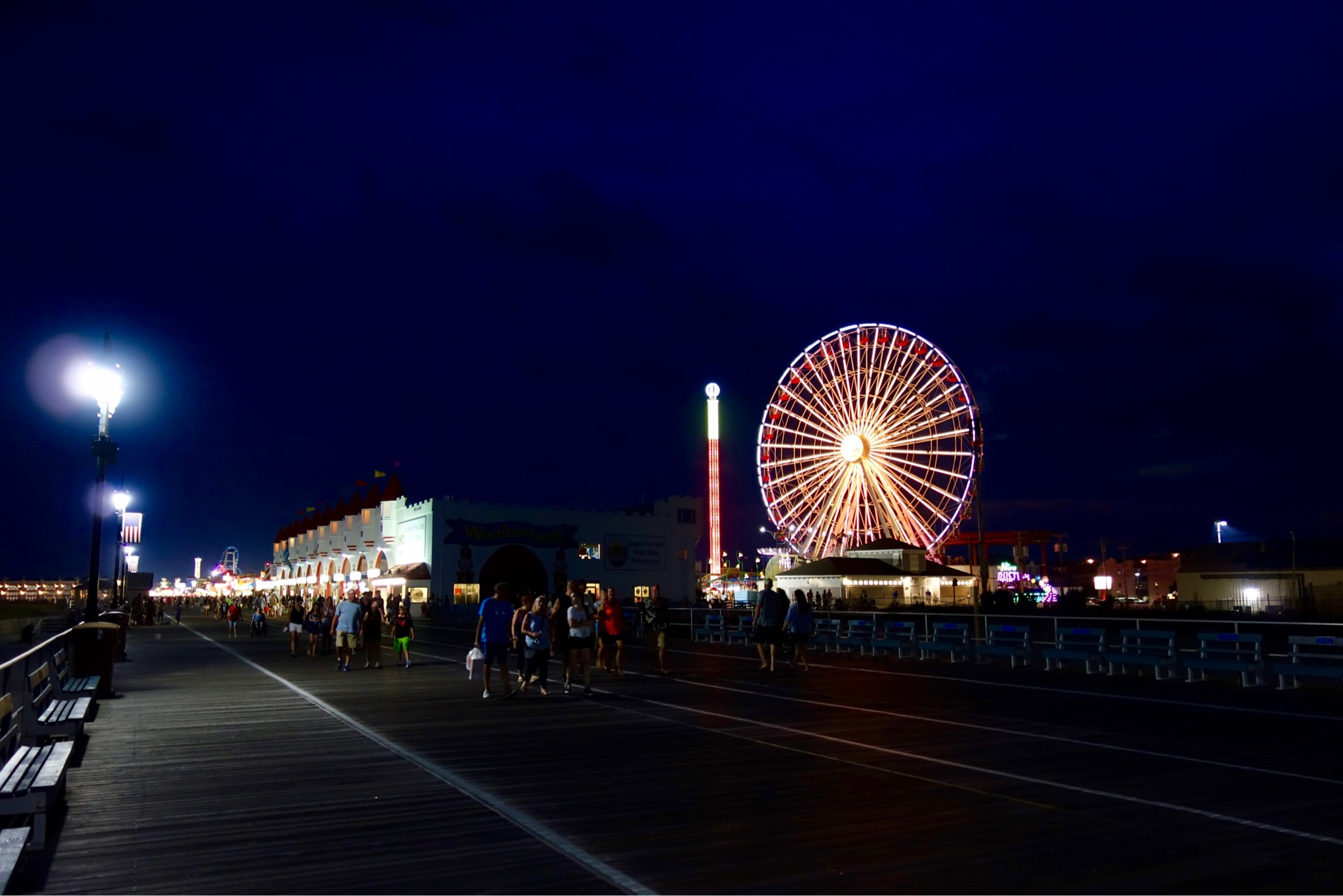 Ferris wheel lit up at Ocean City and people walking along Promenade