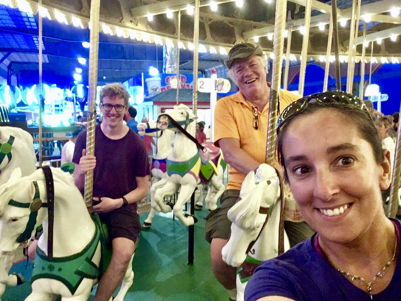 Ben, Steph and Warmshowers host, Tom, on horse carousel in Ocean City, USA