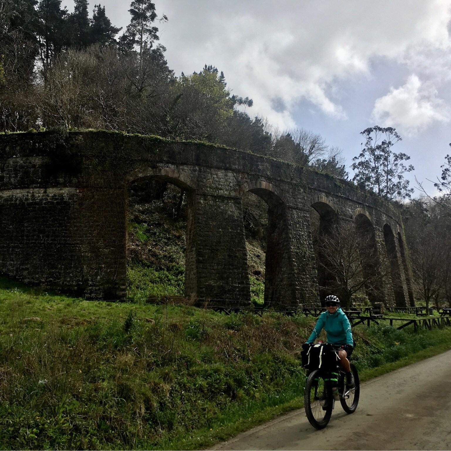 Cycling past an old aqueduct near Santander in Spain