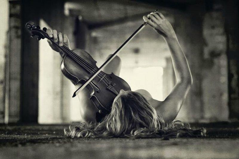 Mujer tumbada tocando un violín, pónmelo difícil