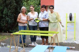 Vier Frauen mit Malutensilien stehen hinter der zu lackierenden Bank