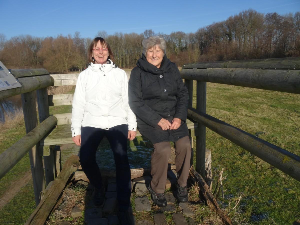 Foto Zwei Wanderer auf einer Bank genießen die Sonne