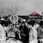 Scharz-Weiß-Bild aus dem Jahr 1972. Mehrere Menschen stehen vor einem Stand auf dem Flohmarkt in Geisweid. Eine Dame hält ein Spinnrad in die Höhe.