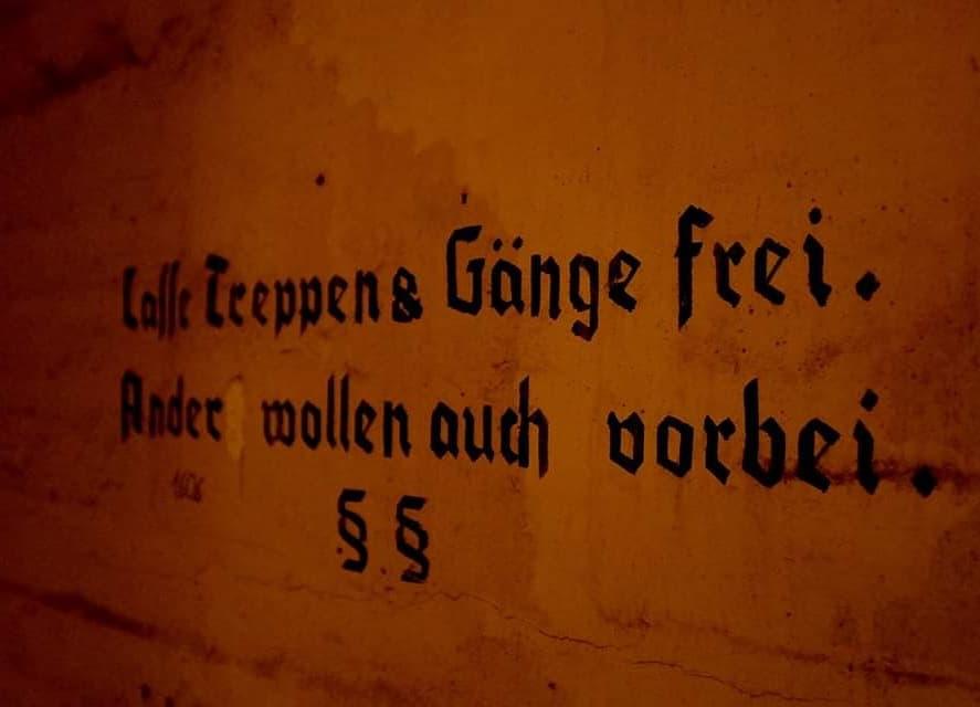 """Auf einer Bunkerwand steht etwas geschrieben. Es sind die Worte """"Lasse Treppen und Gänge frei. Andere wollen auch vorbei."""""""