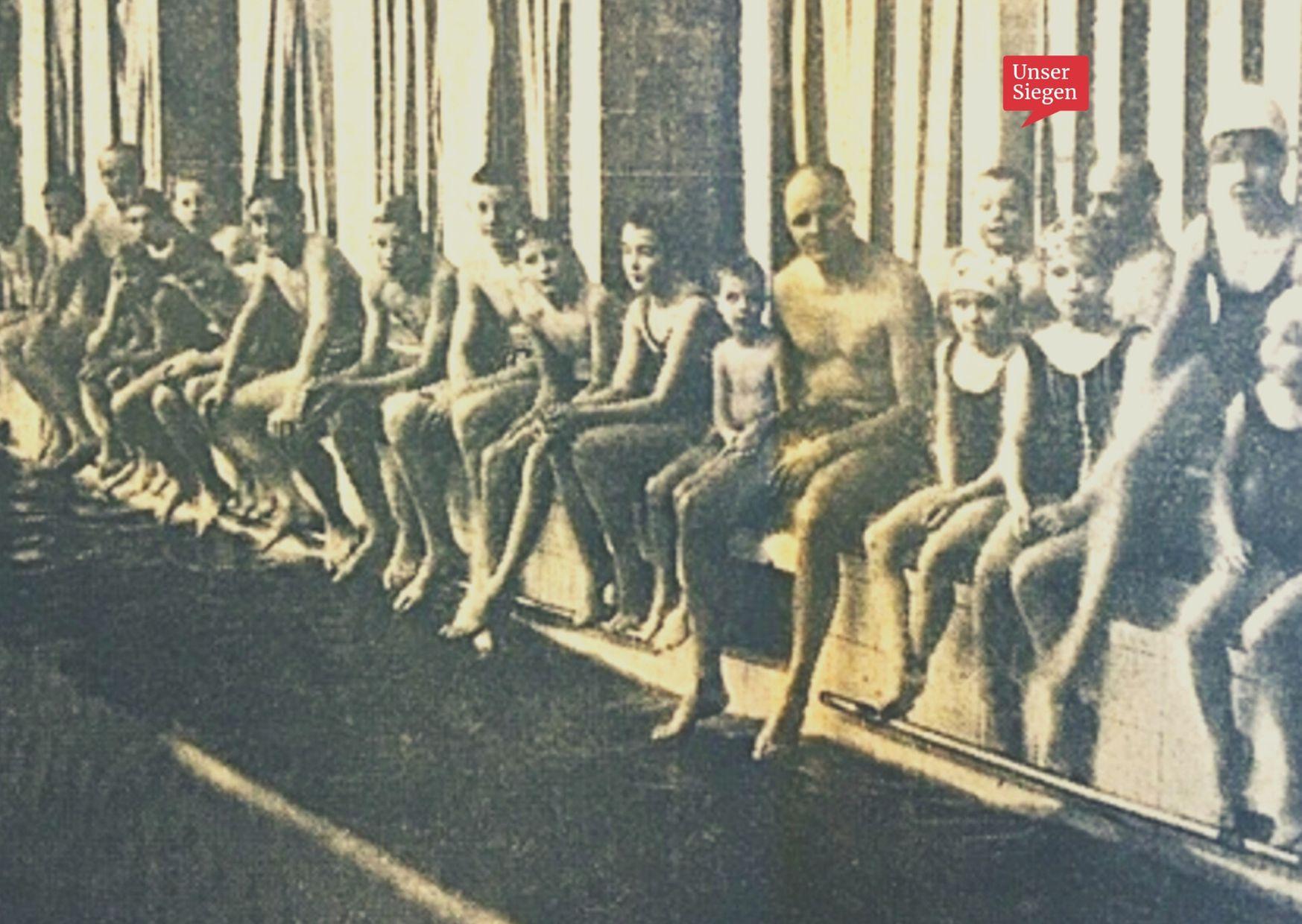 Ein Erwachsener sitzt mit Kindern und Jugendlichen am Beckenrand des alten Jugendstilbades auf der Sieghütte in Siegen. Schwarz-Weiß-Aufnahme von 1966. Mit freundlicher Genehmigung der Siegener Zeitung