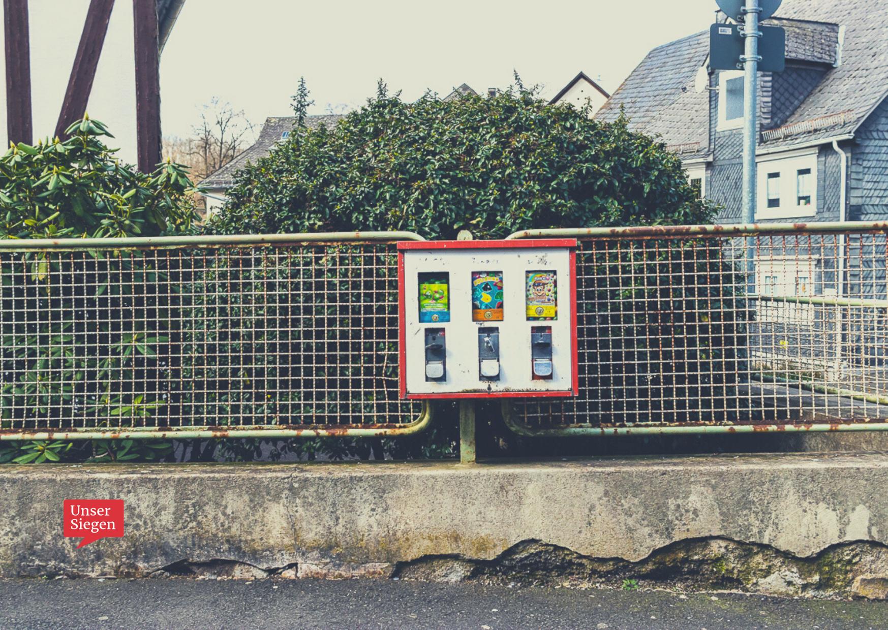 Ein roter Kaugummiautomat am Zaun, im Hintergrund ein typisches Siegerländer Fachwerkhaus. Mit freundlicher Genehmigung von Dr. Michael Meinhard.