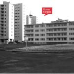 Schwarz-Weiß-Foto mit Hochhäusern und einem kargen Platz im Vordergrund. Mit freundlicher Genehmigung vom Stadtteilbüro Fischbacherberg in Siegen.