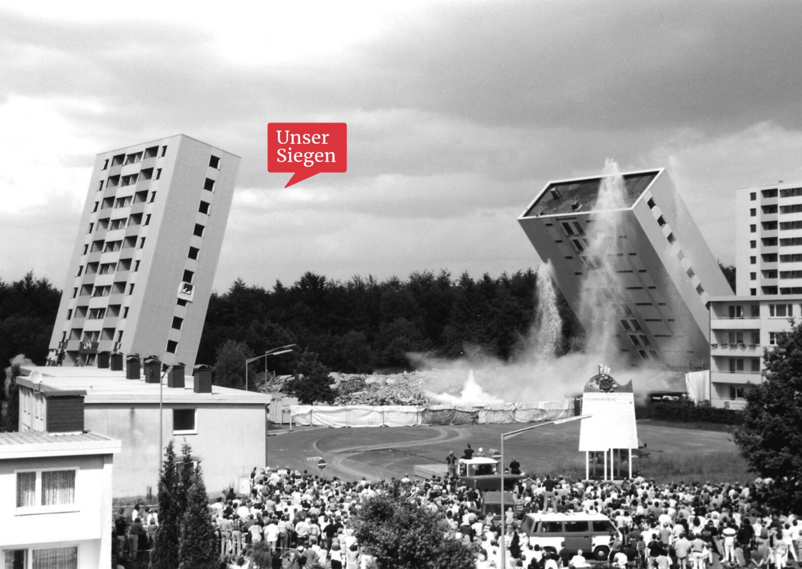 Schwarz-weiß-Foto von 1999, zwei Hochhäuser werden gesprengt und fallen in sich zusammen. Mit freundlicher Genehmigung vom Stadtteilbüro Fischbacherberg in Siegen.