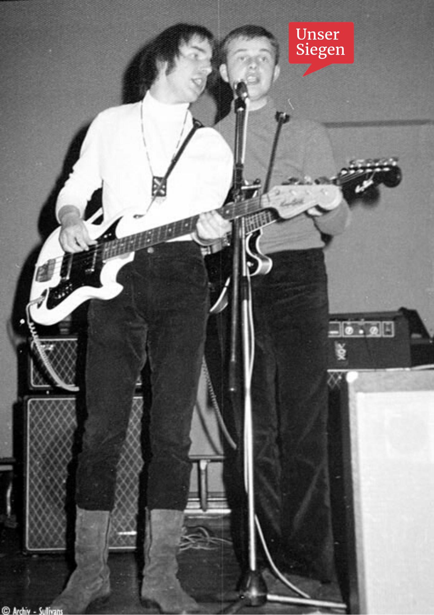 The Sullivans, eine Beatband aus Siegen. Schwarz-weiß-Foto aus den 1960ern, zwei Musiker mit Gitarre und Bass stehen vor einem Mikrofon und singen. Mit freundlicher Genehmigung von Wolfgang Thomas.