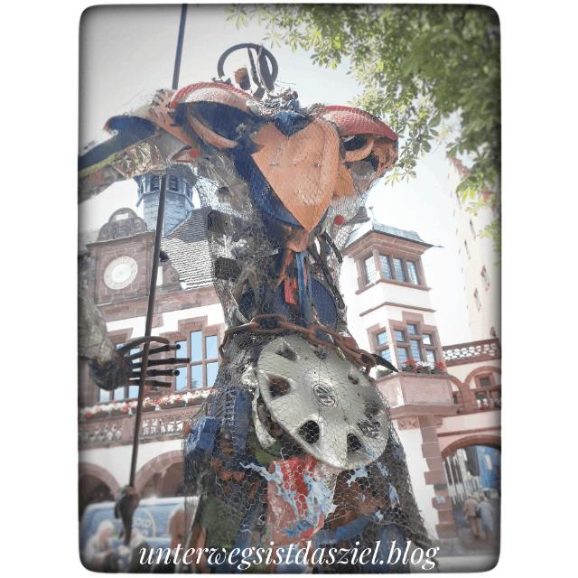 plastikmensch steht vor dem Rathaus